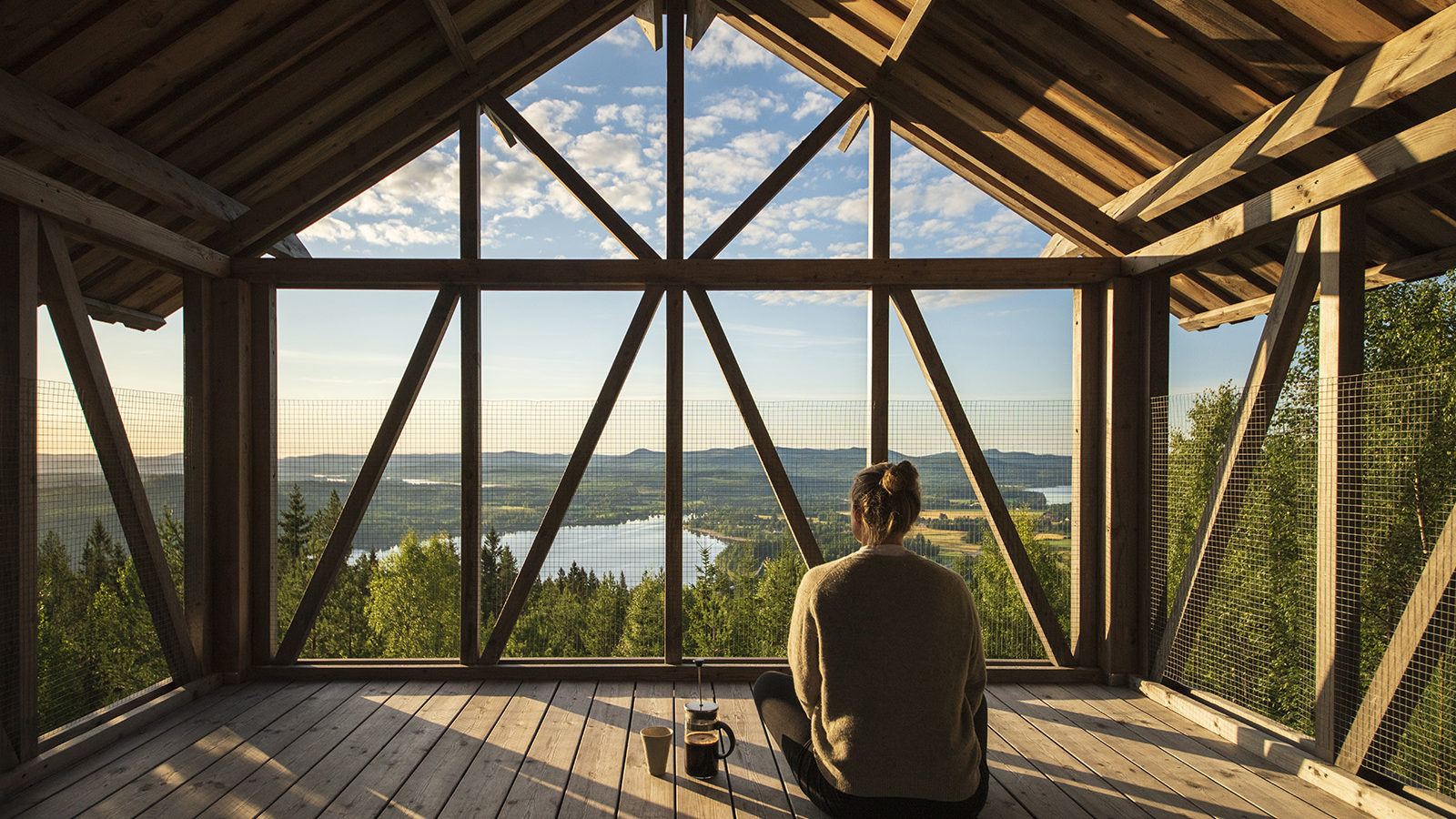 Image of woman sitting in a wooden building with big windows overlooking forests